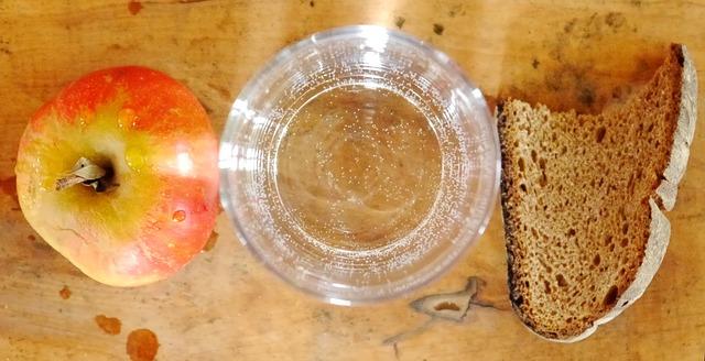 Ein Stück altes Brot liegt neben einem Glas Wasser und einem Apfel.