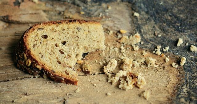 Auf einem Holzbrett liegt ein kleines Stück Brot mit einigen Krümeln