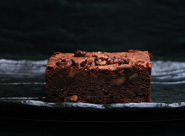 Ein saftiger Brownie mit klein gehackten Nüssen liegt auf einem schwarzen Teller