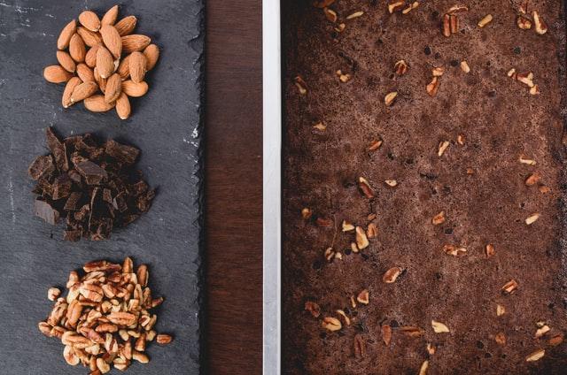 Links liegen drei Haufen aus Mandeln, Walnüssen und gehackter Schokolade, rechts steht der gebackene Teig