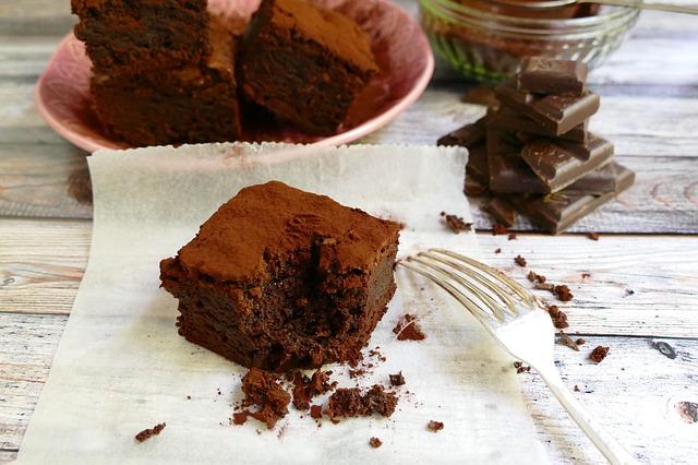 Ein saftiger Brownie, von dem ein Bissen fehlt, liegt auf einem Tisch, daneben eine Gabel, im Hintergrund steht ein Teller mit mehr Brownies