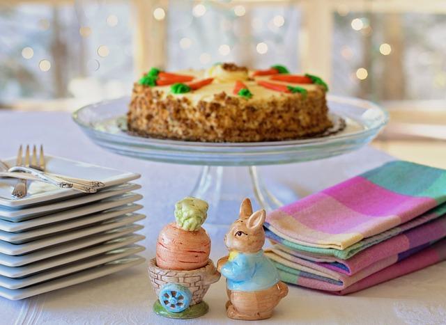Auf einem Glas-Tortenteller steht ein saftiger Karottenkuchen, daneben liegen Servietten, Teller und eine kleine Osterhasenfigur.