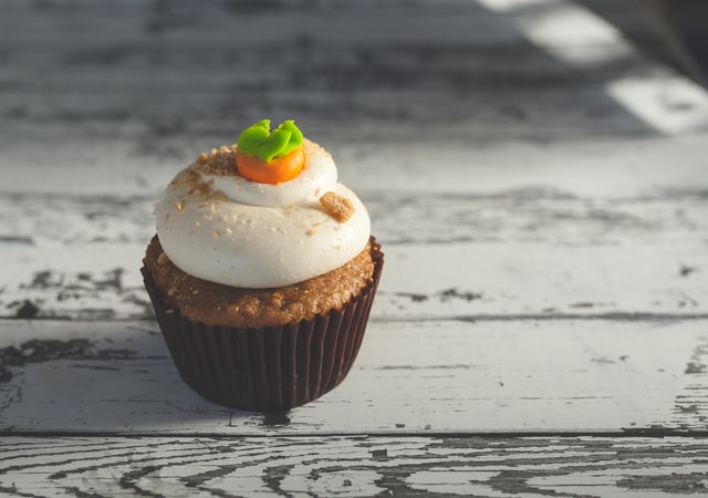 Auf einem Holztisch steht ein kleiner Karottenkuchen-Cupcake.