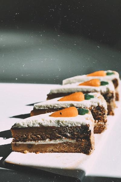 Vier Stücke saftiger Karottenkuchen liegen nebeneinander auf einem Brett.