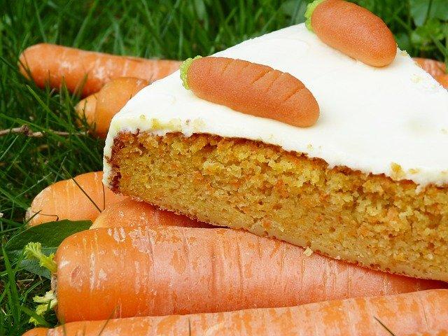 Auf einem kleinen Stapel Möhren, die im Gras liegen, thront ein Stück Karottenkuchen.
