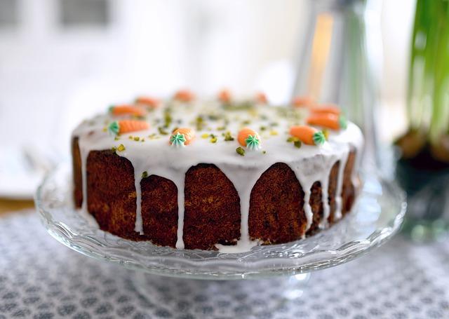 Auf einem Tortenständer aus Glas steht ein saftiger Karottenkuchen