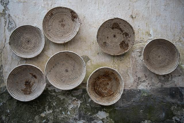 Mehrere flache Gärkörbe stehen nebeneinander auf einem Steinboden