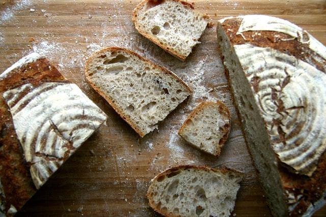 Ein frischgebackenes Brot mit Muster in der Kruste liegt angeschnitten auf einer bemehlten Holzfläche
