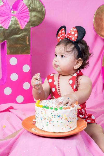 Ein kleines Kind mit Mausohr-Haarreif sitzt und isst mit den Händen eine Torte