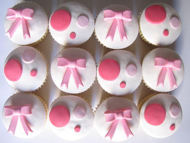 Kleine Cupcakes mit Kreisen und Schleifen aus Fondant stehen auf einem weißen Untergrund