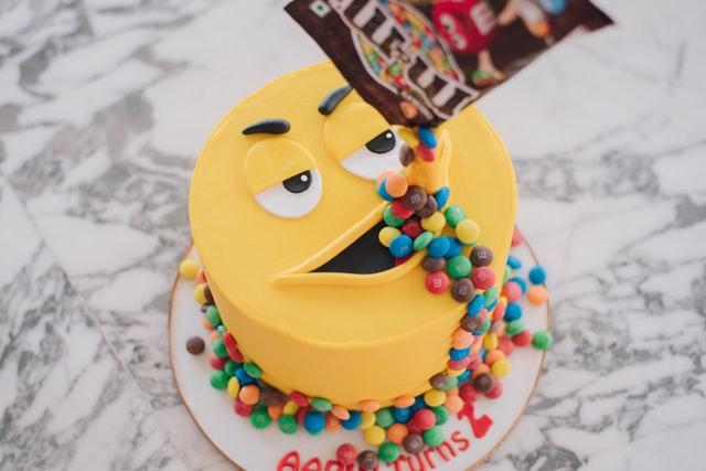 Ein Gebrutstagskuchen für Kinder sieht aus wie ein großer gelber M&M, dem Schokolinsen aus dem Mund laufen.