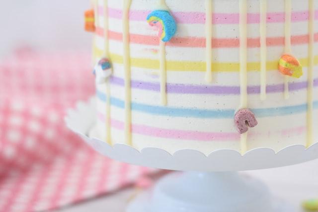 Auf einer Tortenplatte steht ein Regenbogenkuchen mit Glasurtropfen an der Seite, dessen Schichten von außen zu sehen sind