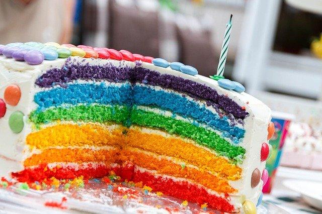 Ein aufgeschnittener Regenbogenkuchen mit Cremeschicht drumherum und bunten Schokolinsen ist zu sehen