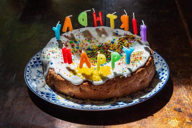 Auf einem Teller steht ein mit dickem Zuckerguss, bunten Streuseln und Buchstabenkerzen verzierter Rührkuchen