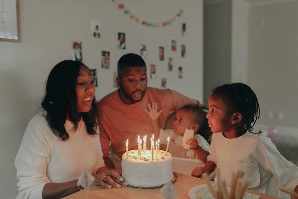 Um einen gedeckten Tisch sitzt eine Familie mit zwei Kindern, in der Mitte steht ein Geburtstagskuchen