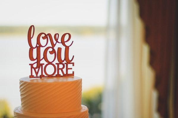 """Auf einer Hochzeitstorte steht ein Schild auf dem """"love you more"""" zu lesen ist"""