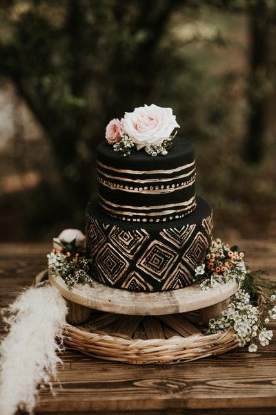Auf einem kleinen Holztableau steht eine zweistöckige schwarz-goldene Torte mit Blütendeko.
