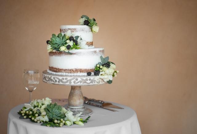 Auf einer Etagere steht eine zweistöckige runde Hochzeitstorte mit Beeren, weißen Blüten und Sukkulenten als Deko