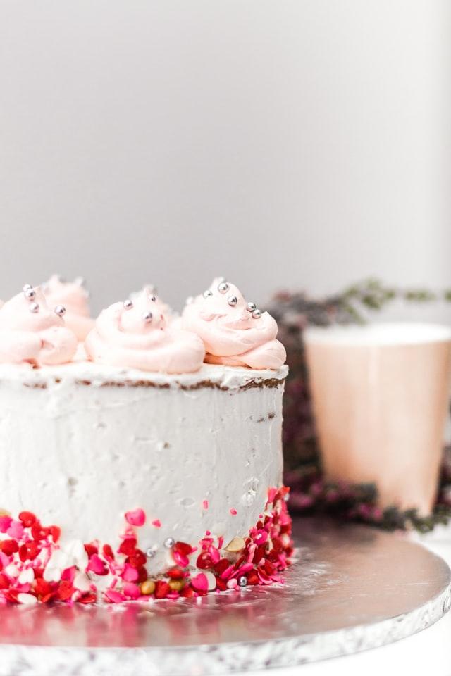 Eine Torte mit Sahnehäubchen oben und roten und pinken Streuseln an der Seite steht auf einem Tisch.