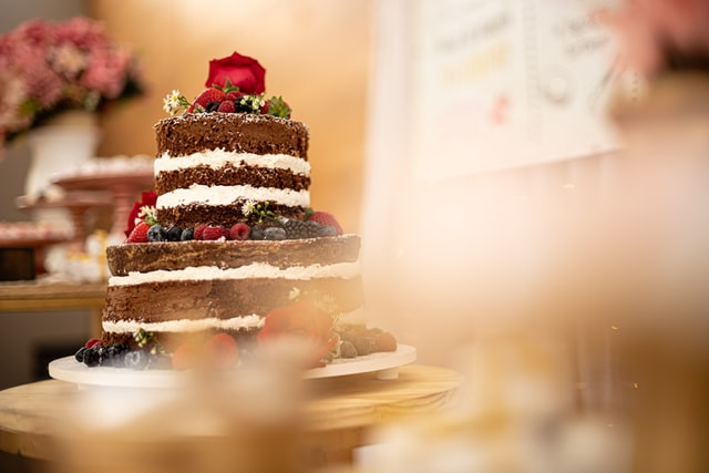 Eine mehrstöckige Torte mit dunklen Böden und heller Creme ist mit Beeren verziert