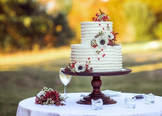Auf einem Tisch im Freien steht eine Hochzeitstote mit Blumendeko.