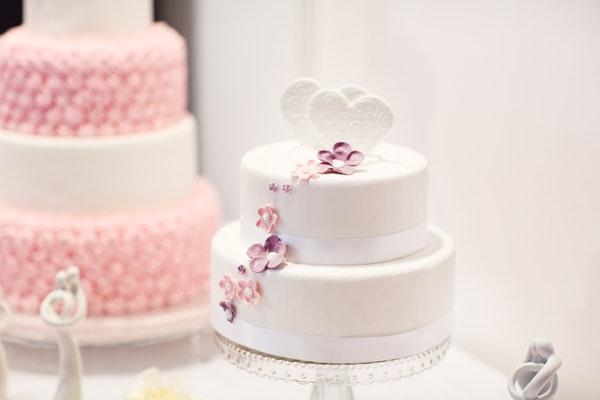 Eine zweistöckige, mit weißem Fondant eingedeckte Torte wurde mit lilanen Blüten und Zwei Herzen verziert