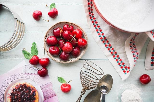 Auf einem Tisch stehen und liegen verschiedene Backutensilien, in der Mitte steht eine Schüssel mit Kirschen.