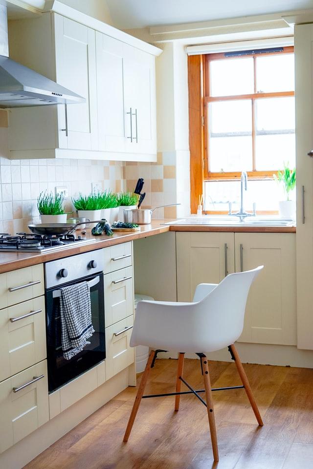 In einer Küche mit hellen Möbeln steht vorm Backofen ein weißer Stuhl.