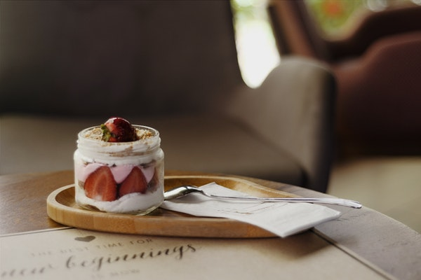 Auf einem kleinen Holztablett steht ein Kuchen im Glas mit Erdbeeren, daneben liegt ein Löffel