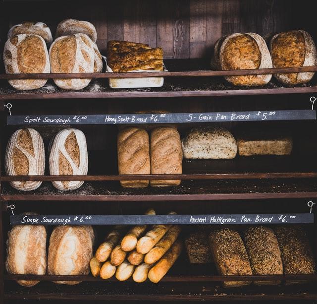 In einem Regal liegen viele verschiedene Brote mit unterschiedlichen Einschnittmustern
