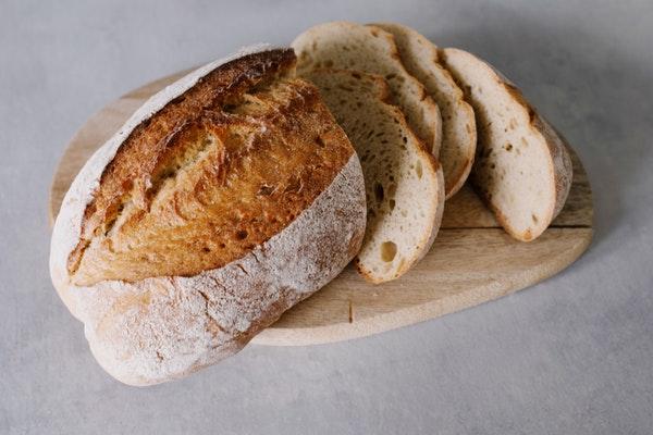 Auf einem Holzbrett liegt ein Brot mit Einschnitt, daneben einige Scheiben desselben.