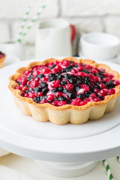 Auf einer weißen Kuchenplatte steht eine Tarte mit verschiedenen Beeren