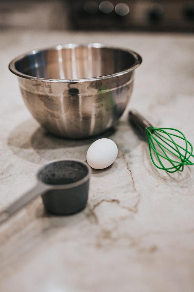 Neben einer Metall-Rührschüssel liegen ein Ei, ein Schneebesen und ein Messlöffel