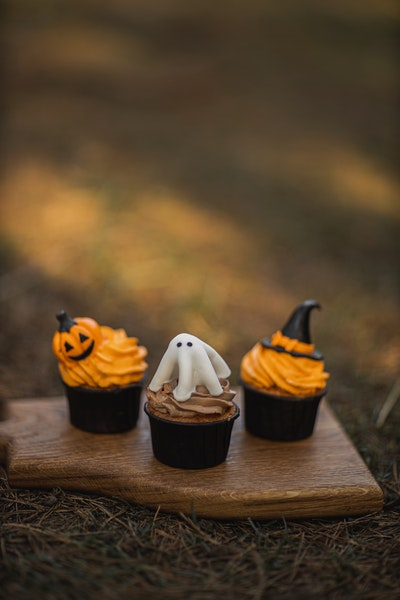 Auf einem kleinen Holzbrett stehen drei unterschiedlich dekorierte Halloween-Muffins.