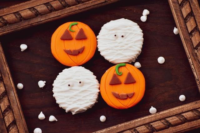 Vier Halloween-Muffins, zwei Mumien, zwei Kürbisse, liegen auf einem Tablett nebeneinander