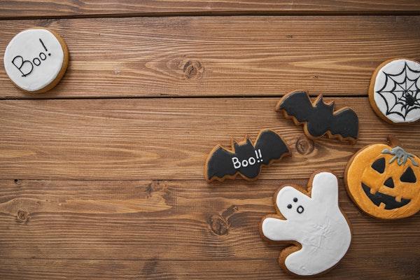 Auf einem Holzuntergrund liegen verschiedene Halloween-Kekse