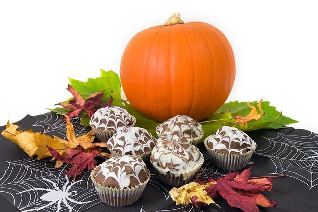 Vor einem großen, orangenen Kürbis stehen einige Halloween-Muffins mit Spinnennetz-Deko