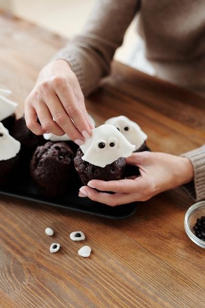 Eine Person dekoriert Halloween-Muffins mit kleinen Geistern