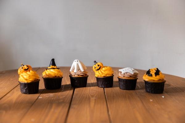 Unterschiedlich dekorierte Halloween Muffins stehen in einer Reihe