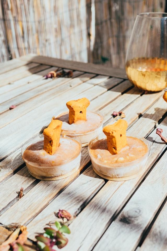 Hundeleckerlis im Glas mit Hundekeks stehen auf einem Tisch