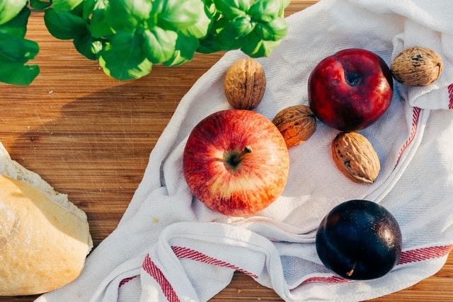 Auf einem Handtuch liegen einige Walnüsse neben zwei Pflaumen und einem Apfel
