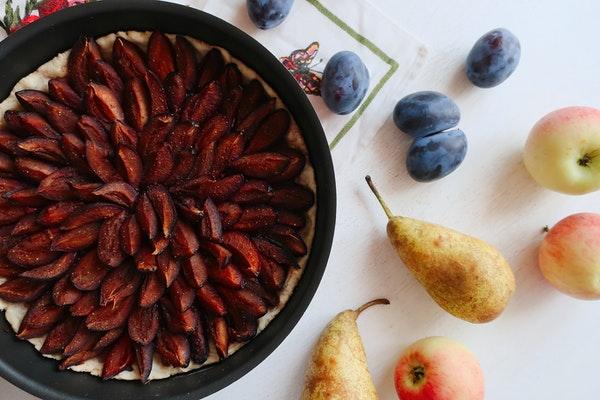 Auf einem Tisch steht in einer Springform ein Pflaumenkuchen, daneben liegt verschiedenes Obst