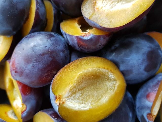Halbiert und entsteinte Zwetschgen liegen gemeinsam mit ganzen Früchten auf einem kleinen Stapel